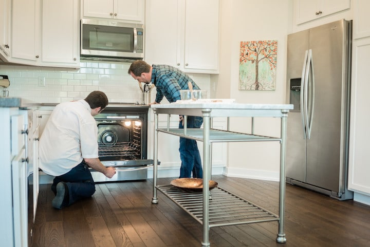 two men inspect a possibly broken stove