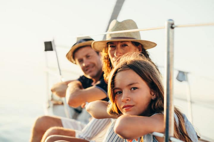 A husband, wife, and their teenage daughter lean over the side of a boat on a sunny day